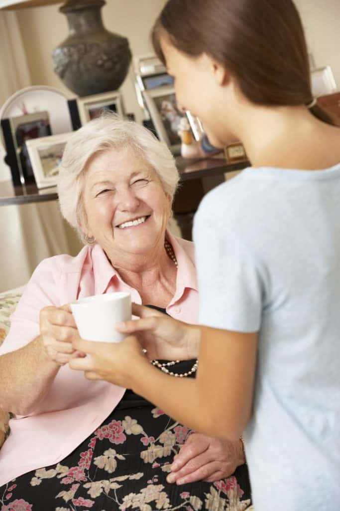 home care worker offers cup of tea to older lady