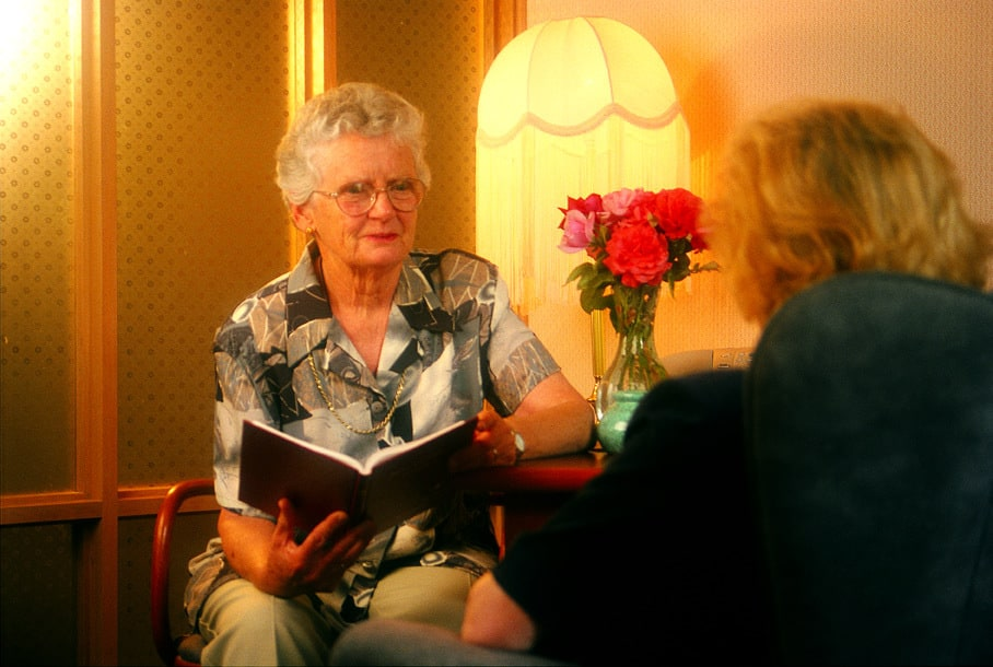 Mrs Glenda McDonald sitting while showing a book to a middle aged woman