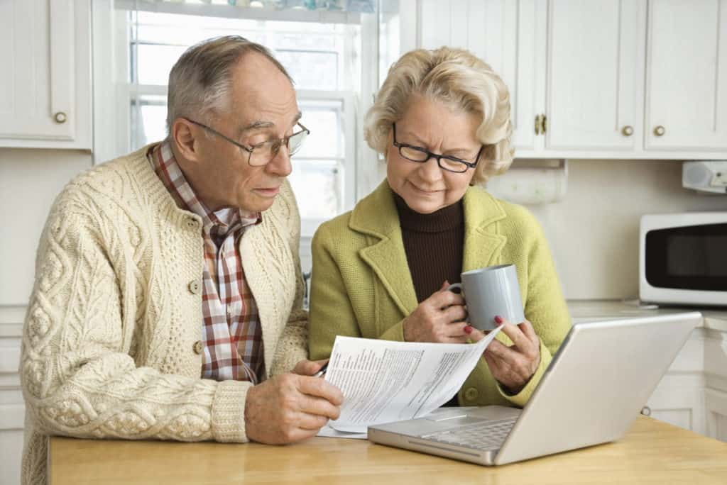 Elderly couple looking at paperwork together while drinking coffee