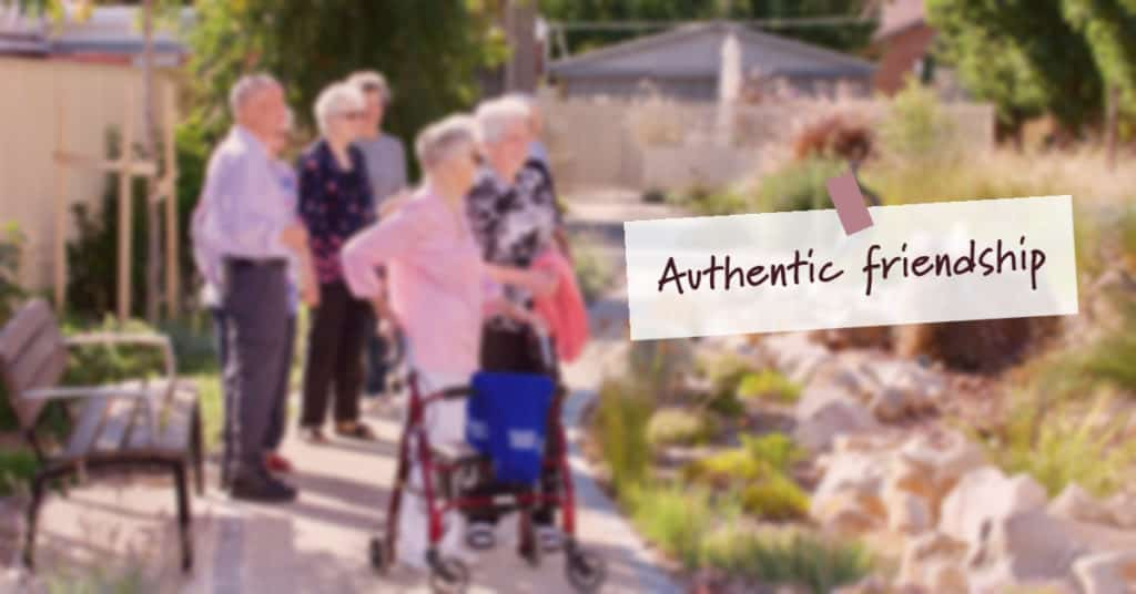 """Group of elderly in a garden with text saying """"Authentic Friendship"""""""