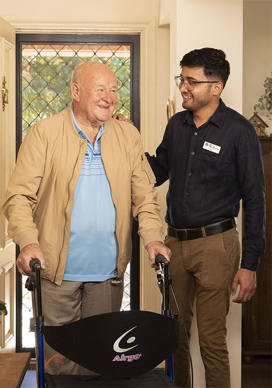 elderly man entering his home with carer