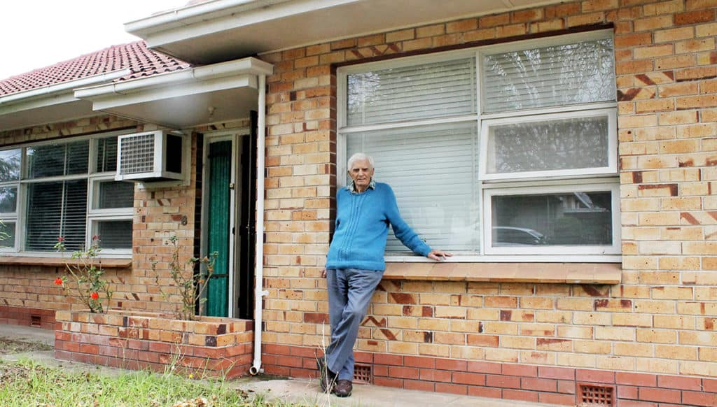 Elderly man leaning against window sill of his house