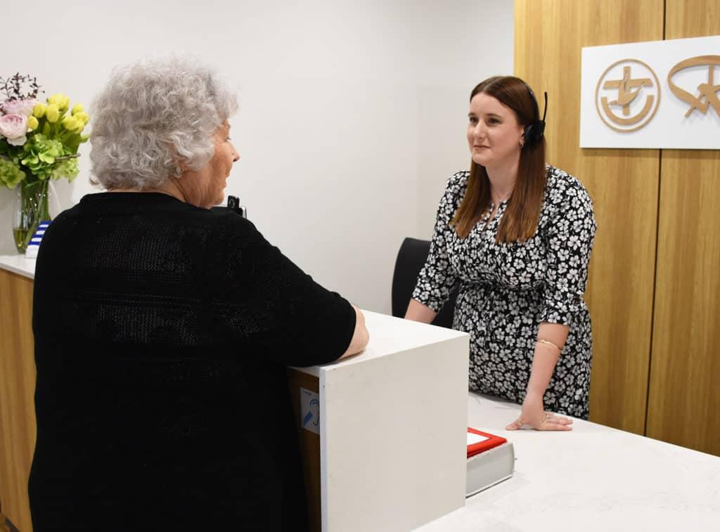 Elderly woman talking to service desk staff