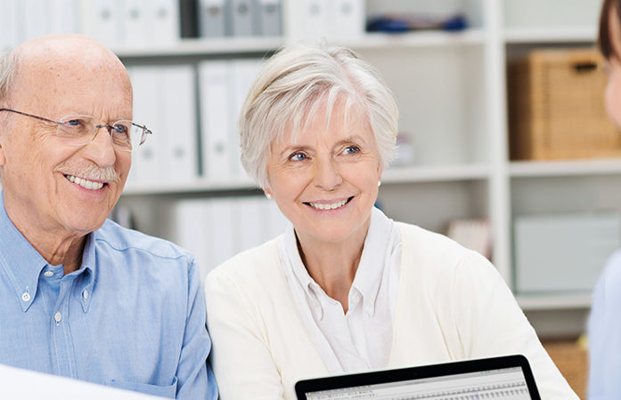 Elderly couple in office smiling at receptionist